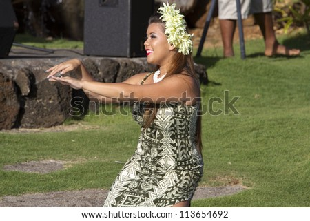 KAUAI, HAWAII - AUGUST 7: Aloha festival. Attractive young woman in traditional dress performs Hawaiian dance on August 7, 2012 in Lihue, Kauai. - stock photo
