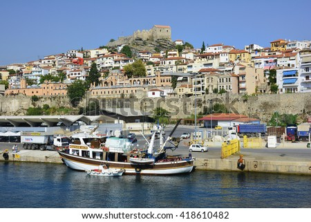 KAVALA, GREECE - SEPTEMBER 18: Fishing ship and cars at ferry terminal in the harbor of the city in Eastmacedonia with Imaret hotel and medieval fortress, on September 18, 2015 in Kavala, Greece
