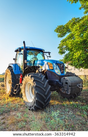 Kavarna, Bulgaria - July 10, 2015: New Holland T7.250 Tractor and blue agricultural trailer on stubble field.