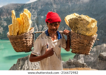 Kawah Ijen, Indonesia - April 24,2010 :  Worker carries sulfur inside Ijen crater  in Ijen Volcano, Indonesia. He carries the load of around 60kg to the top of the rip and then 3km down. - stock photo