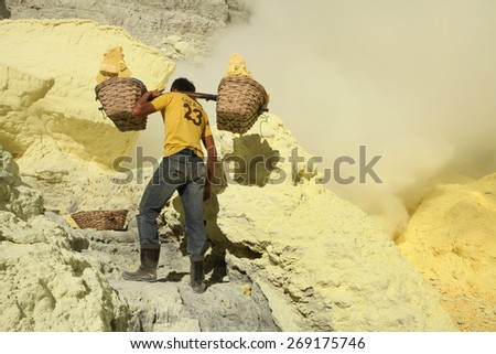 KAWAH IJEN, INDONESIA - AUGUST 8, 2011: Miner carries baskets with sulphur in clouds of toxic volcanic gas at the sulphur mines in the crater of the active volcano of Kawah Ijen, East Java, Indonesia. - stock photo
