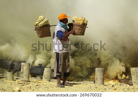 KAWAH IJEN, INDONESIA - AUGUST 8, 2011: Miner carries baskets with sulphur in fumes of toxic volcanic gas at the sulphur mines in the crater of the active volcano of Kawah Ijen, East Java, Indonesia. - stock photo