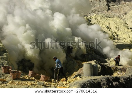KAWAH IJEN, INDONESIA - AUGUST 9, 2011: Miners collect sulphur in the fumes of toxic volcanic gas at s the ulphur mines in the crater of the active volcano of Kawah Ijen, East Java, Indonesia. - stock photo