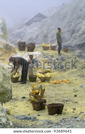 KAWAH IJEN,INDONESIA-JAN 10:Unidentified miner harvests raw sulphur from the crater of Kawah Ijen volcano in hazardous working environment with minimal protection on JAN 10, 2011 in Kawah Ijen - stock photo