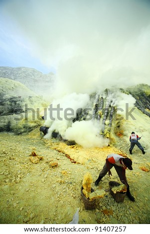 KAWAH IJEN, INDONESIA - SEPT 18 :Sulphur miner harvest raw sulphur from the crater of Kawah Ijen volcano mountain in a very hazardous working environment for a meager USD6 daily wages on 18 Sept 2010 in Kawah Ijen. - stock photo