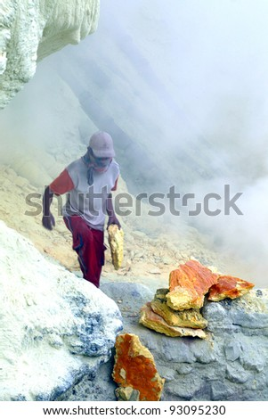 KAWAH IJEN,INDONESIA-SEPT 19:Unidentified miner harvests raw sulphur from the crater of Kawah Ijen volcano in hazardous working environment with minimal protection on Sept 19,2010 in Kawah Ijen - stock photo
