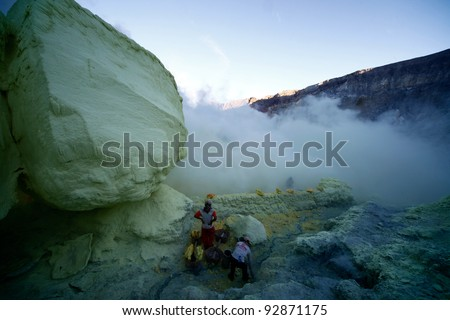 KAWAH IJEN, INDONESIA - SEPT 19 : Unidentified miners harvest raw sulphur from the crater of Kawah Ijen volcano in hazardous working environment with minimal protection on Sept 19, 2010 in Kawah Ijen.