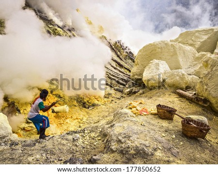 KAWAH IJEN VOLCANO, EAST JAVA, INDONESIA - MAY 25, 2013: Sulfur miner extracting sulfur from inside the crater of Kawah Ijen volcano in East Java, Indonesia.  - stock photo