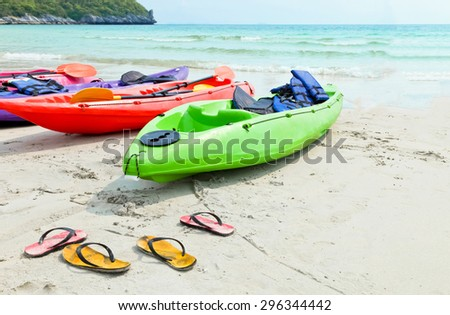 Kayak and Flipflops on a sandy ocean beach soft focus. - stock photo