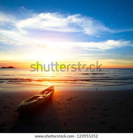 Kayak on the beach at sunset. - stock photo