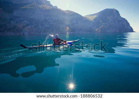 Kayak. People kayaking in the sea with calm blue water near the mountains. - stock photo