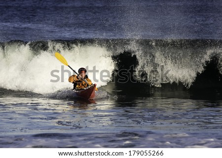 Kayak surfer with expressive face escaping from big wave on rough sea in Black Cove, Nova Scotia coast, Canada - stock photo