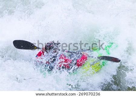 Kayaker Battling White Water Rapids - stock photo