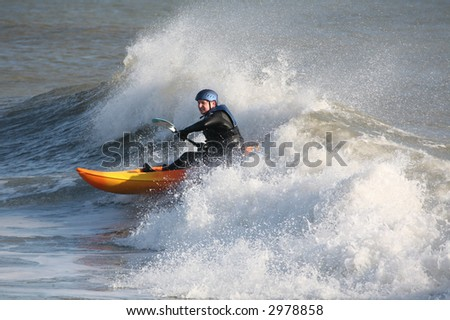 Kayaker on the crest of a wave in rough seas - stock photo