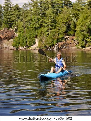 Kayaker under a small waterfall - stock photo