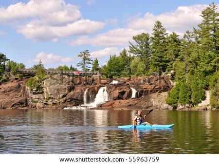 Kayaker under waterfalls - stock photo