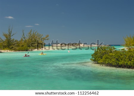 kayakers headed out of a harbor at Cat Island Bahamas - stock photo