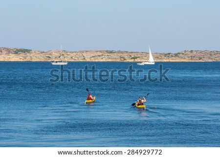 Kayakers in the sea at rocky coast - stock photo