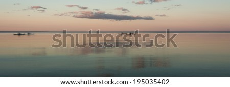 Kayakers on a lake at sunset, blurred by long exposure.  Mackinac Island, MI, USA. - stock photo