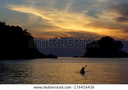 Kayakers silhouette on ocean during orange sunset - stock photo