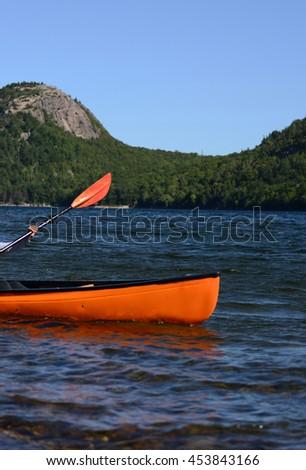 Kayaking in Maine in an orange kayak - stock photo