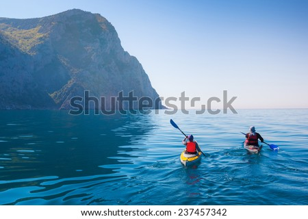 Kayaking in the sea from back view . - stock photo