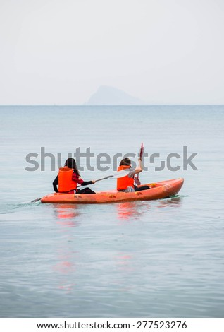 kayaking in the thai ocean from backward view - stock photo