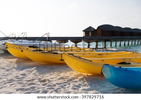 kayaking, leisure, water sport and summer vacations concept - canoes or kayaks mooring on sandy beach - stock photo