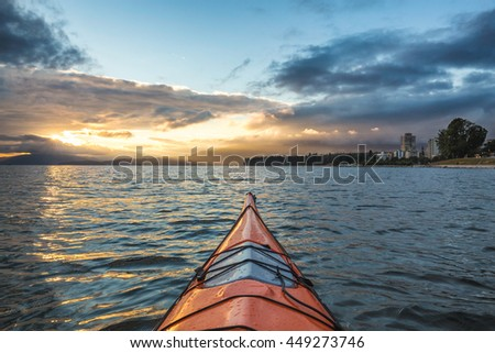 Kayaking near English Bay in Downtown Vancouver, BC, Canada, during a beautiful cloudy sunset with sun rays.
