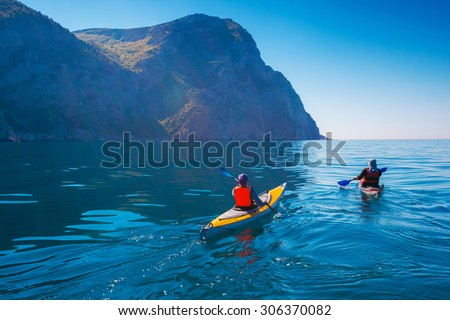 Kayaking. People swim in the sea kayak near the mountains. Adventures on the water. - stock photo