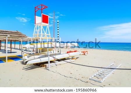 Kayaks and lifeguard tower on sandy Porto Giunco beach, Sardinia island, Italy  - stock photo