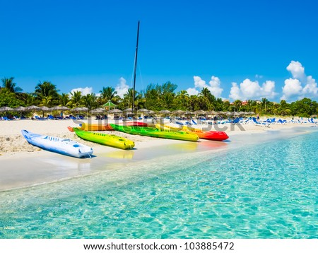 Kayaks and sailing boats on the beautiful beach of Varadero in Cuba (image taken from the sea) - stock photo