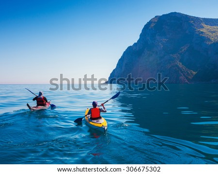 Kayaks. Couple kanoeing in the sea near the island with mountains. People kayaking in the ocean. - stock photo