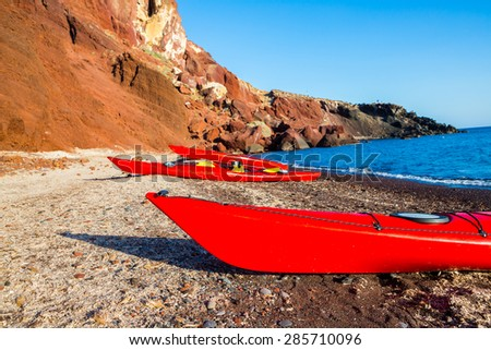 kayaks on the red rocks beach - stock photo