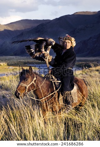 Kazakh men traditionally hunt foxes and wolves using trained golden eagles. Olgei,Western Mongolia.  - stock photo