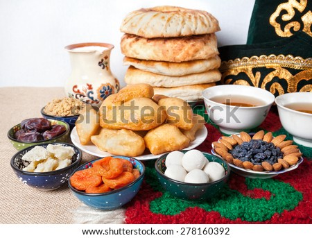 Kazakh national food on the table with national hat and tea at white background  - stock photo