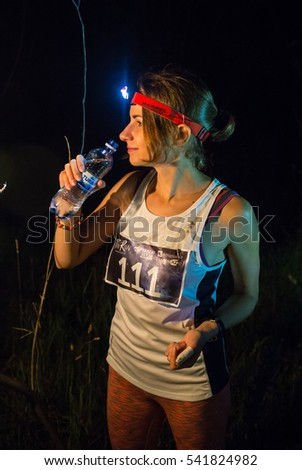 KAZAKHSTAN, ALMATY - 09 JULY 2016: Night trail running competitionsTunRun that took place in the tract Kok Zhailau. Beautiful fitness athlete woman drinking water after work out exercising on sunset