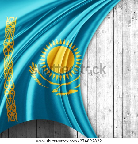 Kazakhstan flag of silk and wood background - stock photo