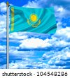 Kazakhstan waving flag against blue sky - stock photo