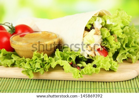 Kebab - grilled meat and vegetables, on bamboo mat, on bright background - stock photo