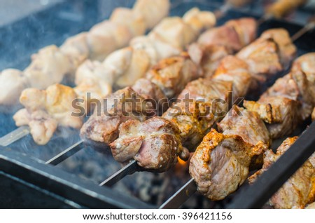 Kebab is fried on the grill skewers . Different kinds of meat - lamb , pork, beef , chicken on the street market . Close-up on the coals. - stock photo