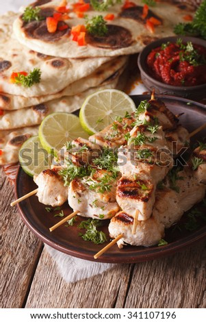 kebabs chicken tikka on skewers close-up on a plate and naan flat bread. vertical