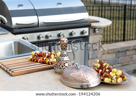 Kebabs ready for grilling on a BBQ arranged on a copper plate and cutting board on the counter of an outdoors summer kitchen alongside a gas grill
