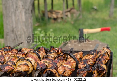 Kebabs sizzling on a grill over a hot BBQ fire with a chopper on a chopping block for cutting the wood and fuel for the fire is visible in the background - stock photo