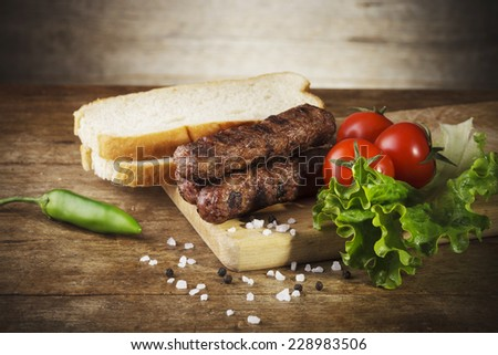 Kebapche Cevapcici with vegetables and bread on wooden board