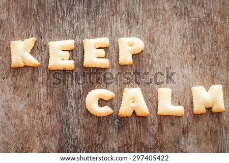 Keep calm alphabet biscuit on wooden table, stock photo - stock photo
