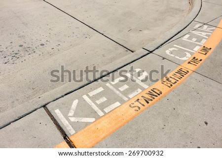 Keep clear safety curb road marking. Yellow painted strip, black and white letters on a pedestrian street.  - stock photo