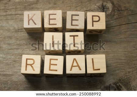 keep it real text on a wooden background - stock photo