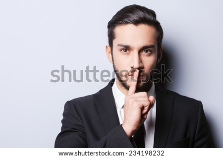 Keep my secret!  Serious young man in formalwear holding finger on lips and looking at camera while standing against grey background - stock photo