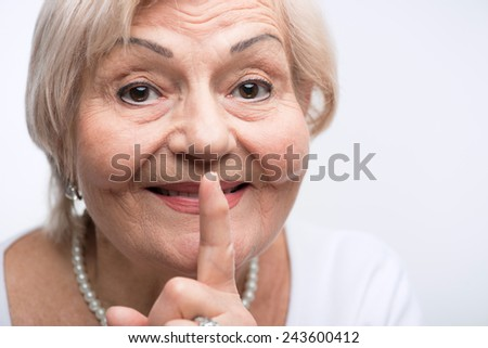 Keep silence. Closeup portrait of elderly woman putting finger to her mouth and smiling while standing against white background - stock photo